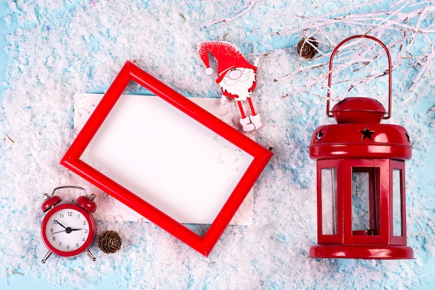 Photo mock up with red frame, clock and lantern on white snow
