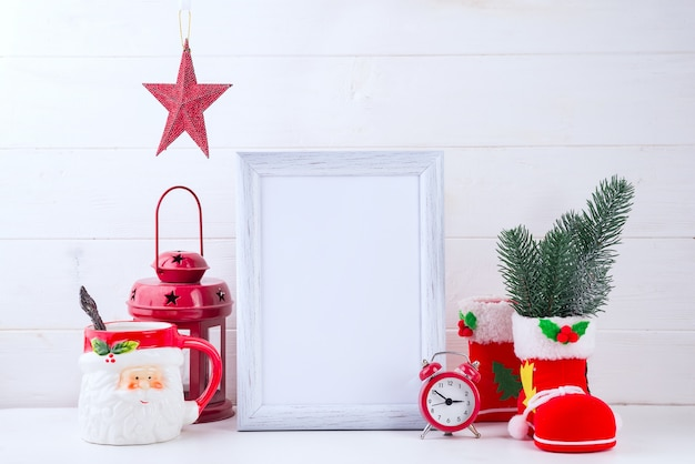 Photo mock up with white frame, poinsettia in a flowerpot and red lantern on white wood