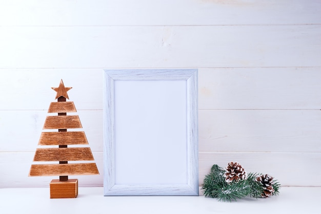Photo mock up with white frame, wooden tree and pine branches on white wood
