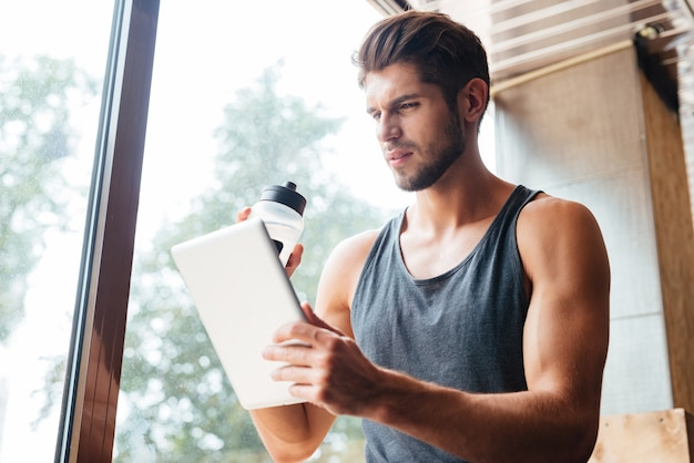 Photo of model in gym with tablet and bottle