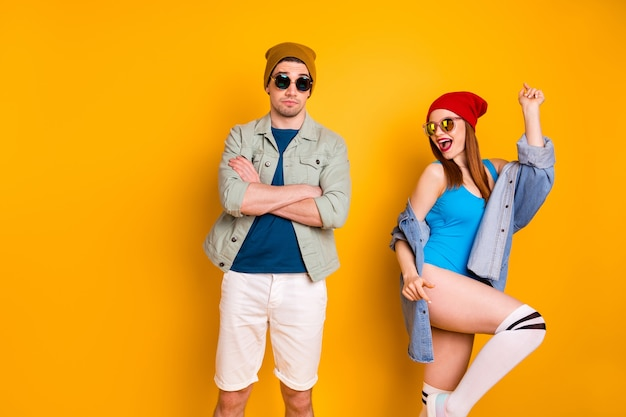 写真現代のカップルの男は大音量のパーティー音楽を嫌うクロスアームガールダンスウェアデニムジーンズジャケット水着長い白い靴下分離された明るい輝き色の背景