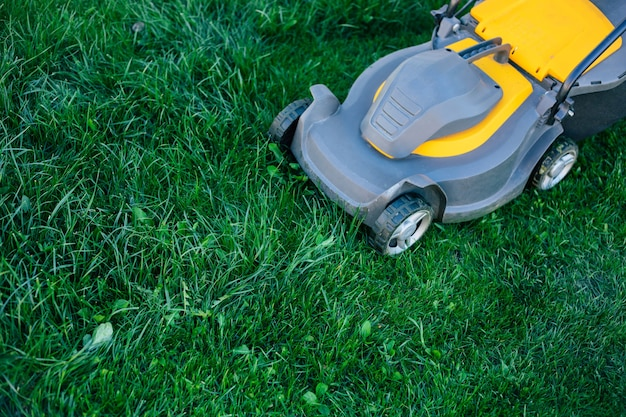 Photo of a modern electric lawn mower standing on a backyard lawn near a house