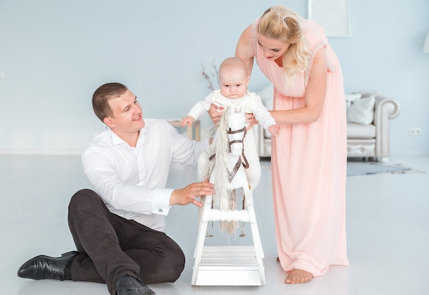 Photo of mom and dad roll their little son on a children's toy horse
