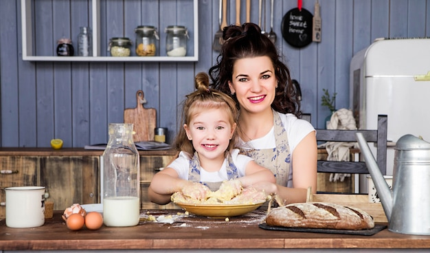 Photo of mom and daughter cook together in the kitchen