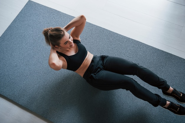 Photo in motion. doing abs on the floor in the gym. beautiful female fitness woman