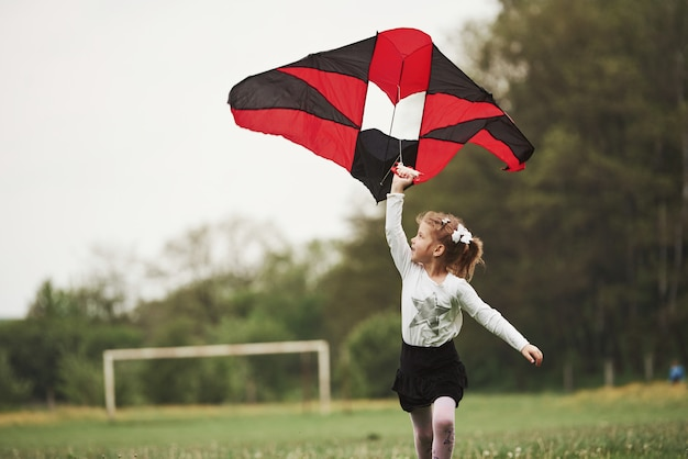 Photo in motion. happy girl in casual clothes running with kite in the field. beautiful nature