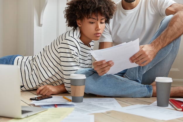 Photo of multiethnic family check balance on papers, drink takeaway coffee, thinks how close bargain