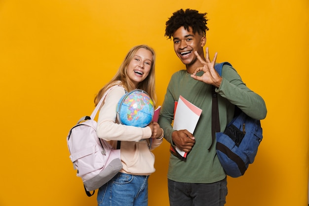 Photo of multiethnic students man and woman 16-18 wearing backpacks holding earth globe and exercise books, isolated over yellow background