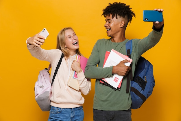 Photo of multiethnic students man and woman 16-18 wearing backpacks taking selfie on mobile phones and holding exercise books, isolated over yellow background