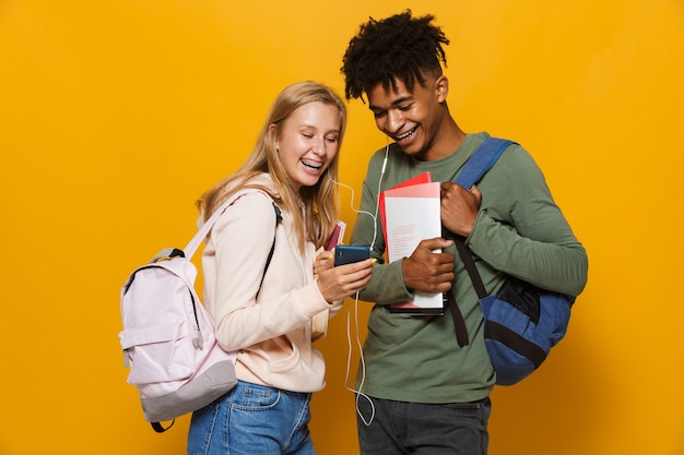 Photo of multiethnic students man and woman 16-18 wearing earphones using mobile phones and holding exercise books, isolated over yellow background
