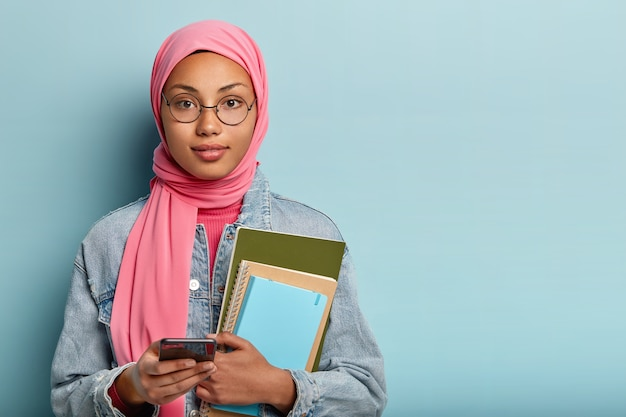Photo of muslim student carries notepad for notes, holds modern cellular, creats new publication in social networks, covers head with veil according to religious rules, chats with groupmates online