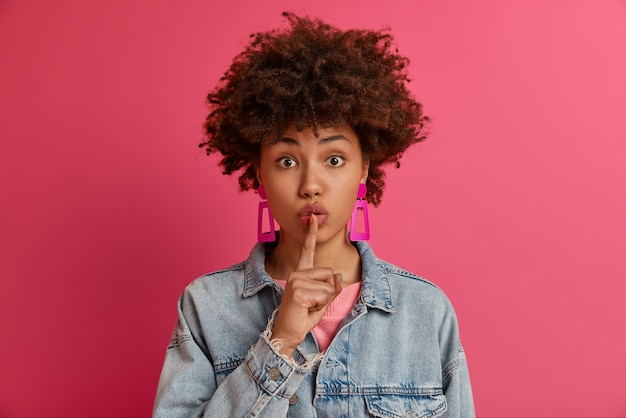 Photo of mysterious young woman has secret plan, makes silence gesture, presses index finger to lips, say keep silent, forbids talking, wears pink earrings and denim jacket, demands be silent