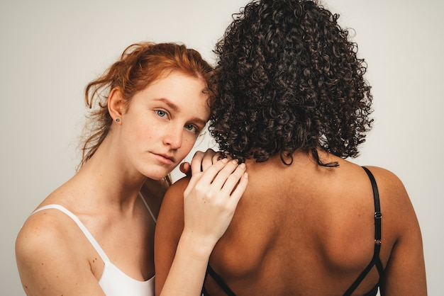 Photo of natural multiracial women, body positive. feminist females in underwear hug and feel support