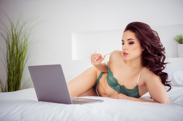 Photo of naughty remote worker lady quarantine online laptop undressing on screen show fit body breast take off bra for money vip customer wear bikini lying sheets linen bedroom indoors
