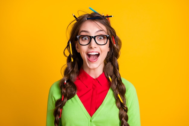 Photo of nerd teenager girl with pencil messy hairdo excited wear green clothes isolated shine color background