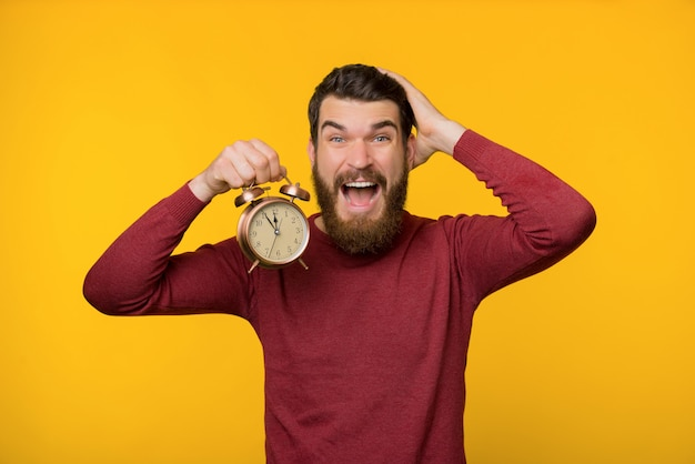 Photo of nervous bearded guy, holding a clock and worried about deadline, standing over yellow background