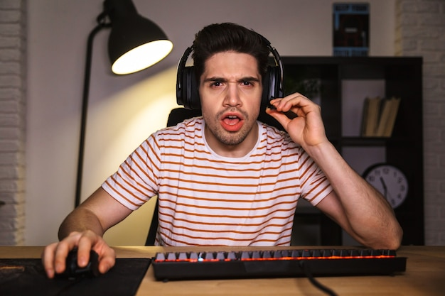 Photo of nervous guy 20s playing video games on computer in room, wearing headphones and using backlit colorful keyboard