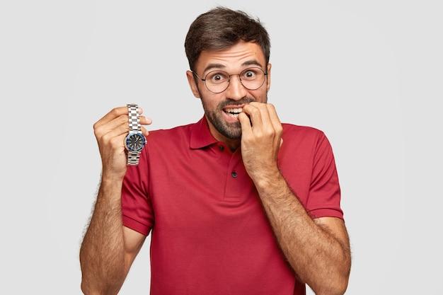 La foto dell'uomo nervoso morde le unghie, ha un'espressione ansiosa