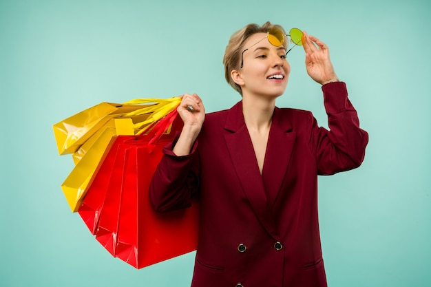 Photo of nice charming girl attractive joyful girl having just ended up shopping and being overjoyed and cheerful while isolated with blue background.