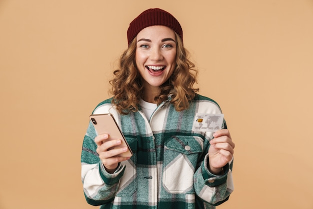 Photo of nice cheerful woman in knit hat holding credit card and cellphone isolated on beige