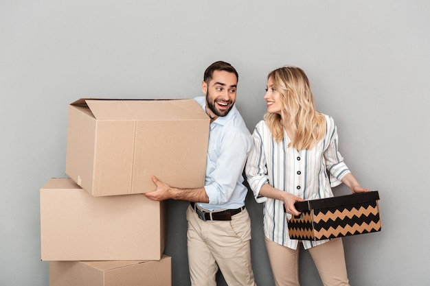Photo of nice european couple in casual clothing looking at each other and carrying cardboard boxes isolated