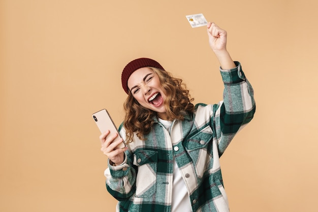 Photo of nice excited woman in knit hat holding credit card and cellphone isolated on beige