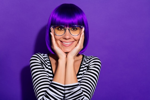 Photo of nice lady hands touch cheeks overjoyed wear wig striped pullover isolated purple background