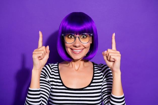 Photo of nice lady indicating index fingers up empty space wear wig striped pullover isolated purple background