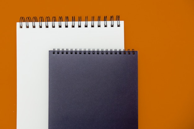 Photo of notepad  on orange background with copy space