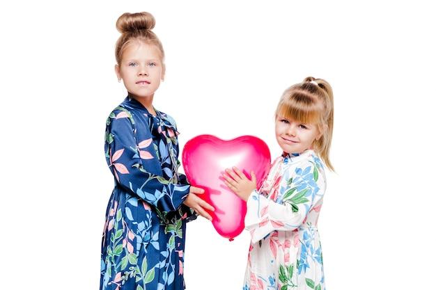 На фото 2 девочки в элегантных платьях держат воздушный шарик в форме сердца.