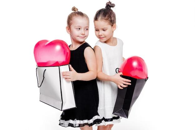 우아한 드레스를 입은 2 명의 어린 소녀 사진이 안에 하트 모양의 풍선이있는 큰 가방을 들고 있습니다.