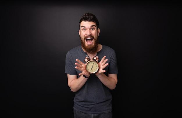 어두운 외진 배경 위에 빈티지 시계를 들고 놀란 수염 난 남자의 사진