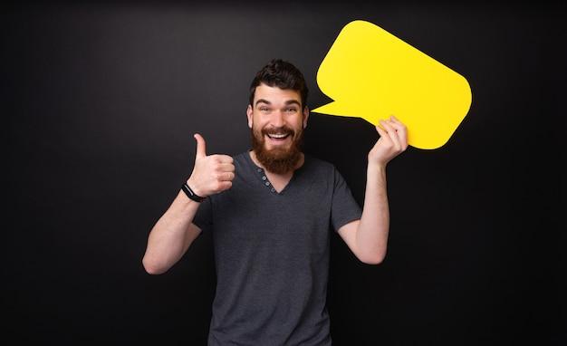 親指を立てて黄色い泡のスピーチを持っているひげを生やした男の写真
