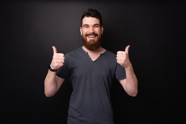 暗い背景の上に親指を見せて歯を見せる笑顔でひげを生やした男の写真