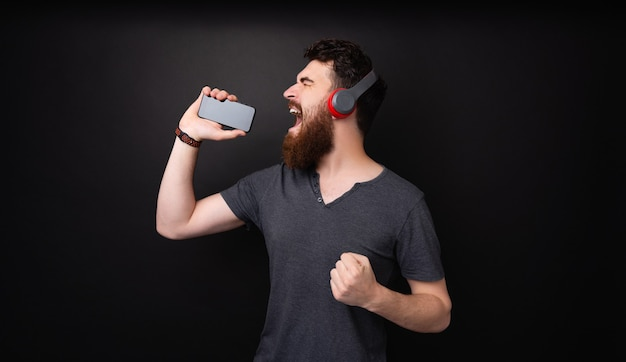 수염 난 남자, 헤드폰으로 음악을 듣고, 마이크처럼 모바일을 사용하는 사진
