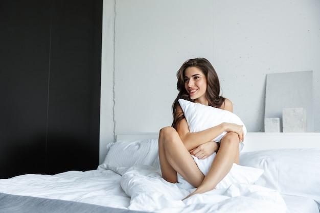 실내 베개를 들고 침대에 앉아 집에서 란제리를 입고 아름 다운 놀라운 행복 갈색 머리 여자의 사진.