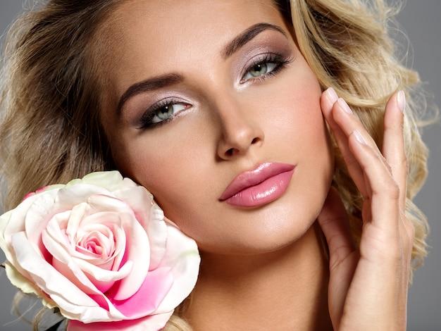 花と美しい金髪の女性の写真。巻き毛の白人女性のクローズアップ魅力的な官能的な顔。スモーキーアイメイク。