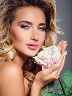 꽃과 함께 아름 다운 금발 여자의 사진입니다. 곱슬 머리를 가진 백인 여자의 근접 촬영 매력적인 관능적 인 얼굴. 스모키 아이 메이크업.