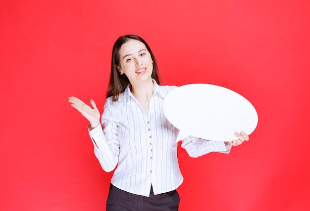 Фотография красивой деловой женщины, держащей пустой речевой пузырь.
