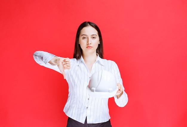 안전 모자를 들고 엄지손가락을 아래로 보여주는 아름 다운 비즈니스 여자의 사진.