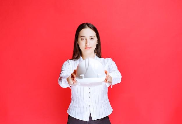 빨간 벽에 안전 모자를 들고 아름 다운 비즈니스 여자의 사진.