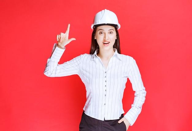 Фото красивой деловой женщины, носящей защитную шляпу, указывая пальцами.