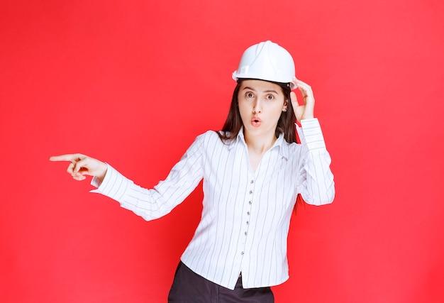손가락으로 멀리 가리키는 안전 모자를 쓰고 아름 다운 비즈니스 우먼의 사진.