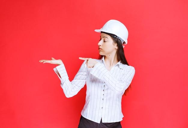 指で離れて指している安全帽子をかぶっている美しいビジネスウーマンの写真。