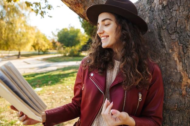책을 읽고 나무 근처 공원에 서있는 아름 다운 귀여운 여자의 사진.