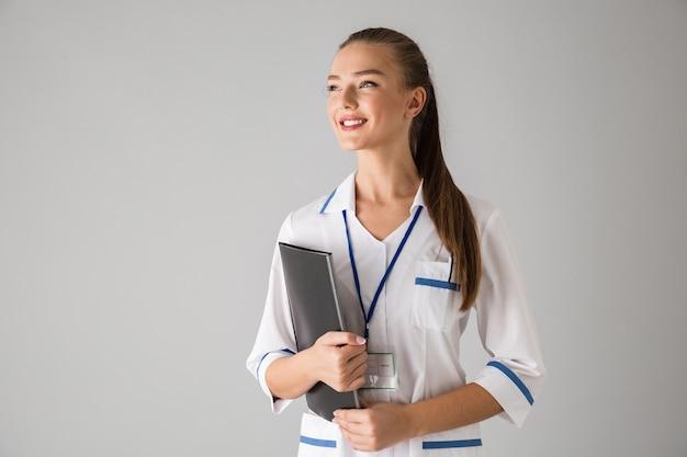 フォルダーを保持している灰色の壁の上に隔離された美しい幸せな若い女性の美容師の医師の写真。