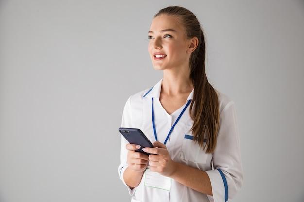 Фотография доктора косметолога красивой счастливой молодой женщины изолированного над серой стеной держа использование мобильного телефона.