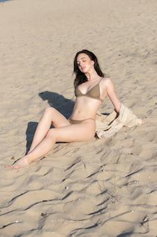 Фото красивой модели в стиле бохо в белом купальнике и серебряных богемных украшениях на пляже на закате