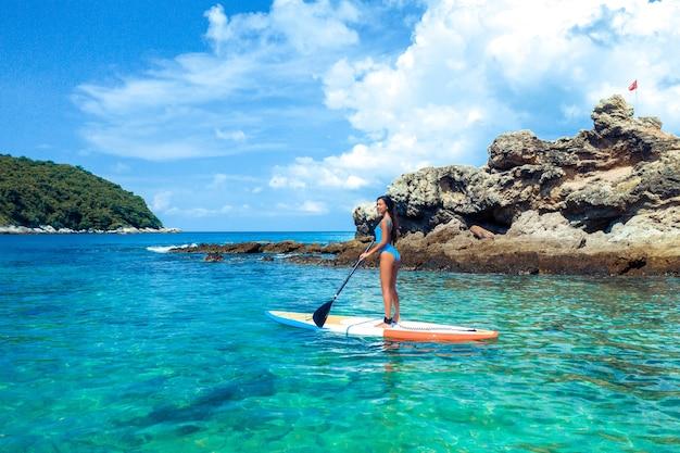 Фотография красивой позирующей девушки, стоящей на каяке с веслом в руке