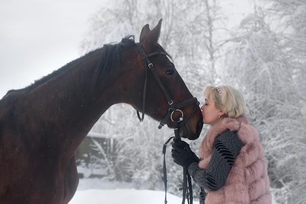 馬にキスをしている美しい女性の写真。